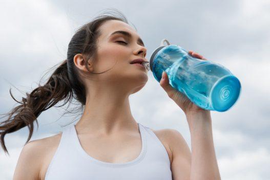Kvinde der drikker af en drikkedunk med sugerør